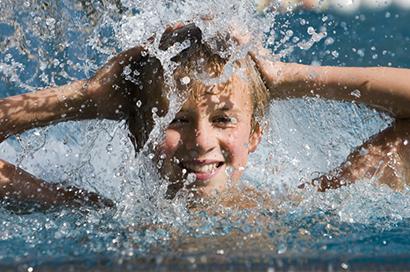 Portrait eines lachenden Jungen im Wasserschwall